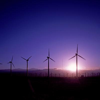 windmolens in een veld met paarse lucht en ondergaande zon